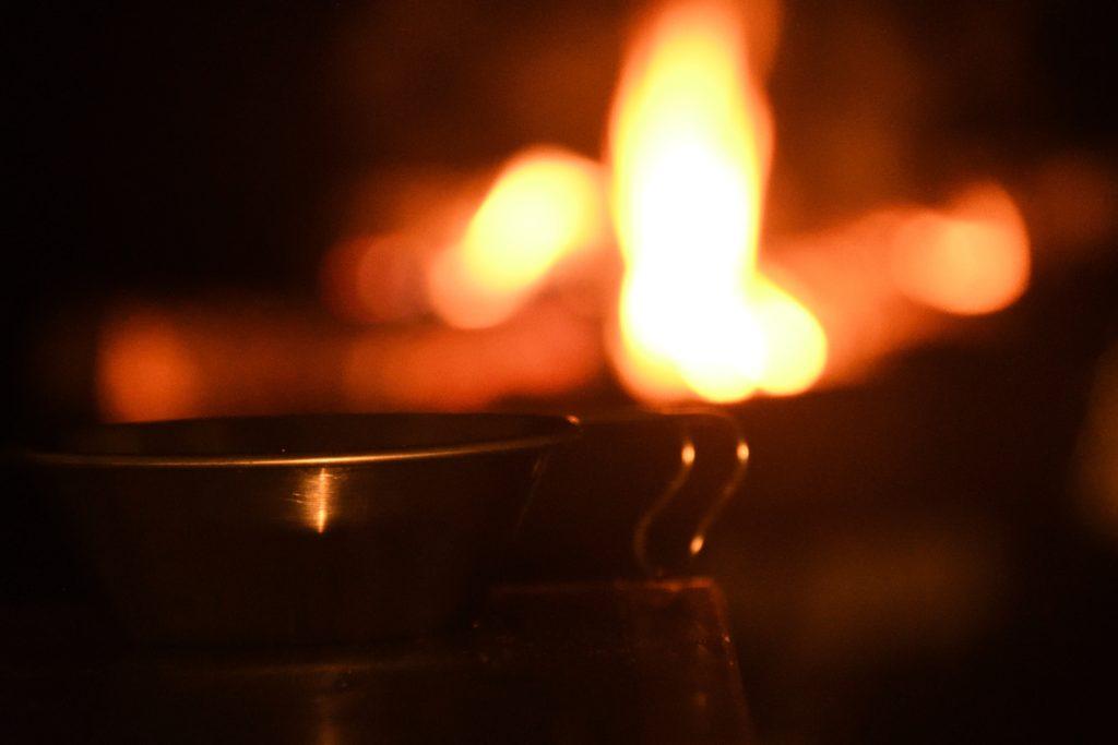 シェラカップに入った味噌汁と焚き火の灯り